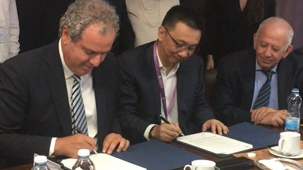 IDE President (l) Yoram Dvash and SDE President Li Qiang sign MOU, while Jacob Korn, President of IsDMA looks on. (Efi Sameach photo)